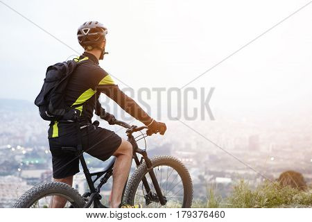Rear Shot Of Young Rider Standing On Top Of Hill With Booster Bike And Looking Down At Foggy City Wh