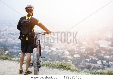 Unrecognizable European Male Cyclist Relaxing On Top Of Mountain, Keeping Hands On Handlebar Of His