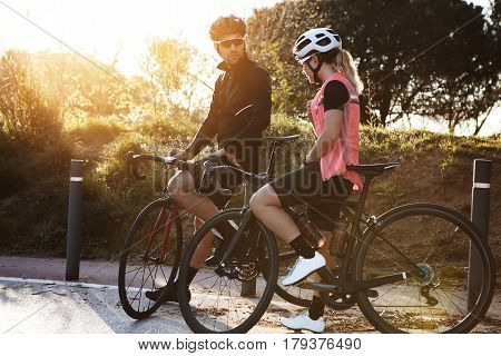 Man And Woman Cyclists Spending Nice Time Together, Talking, Having Rest During Cycling Training In