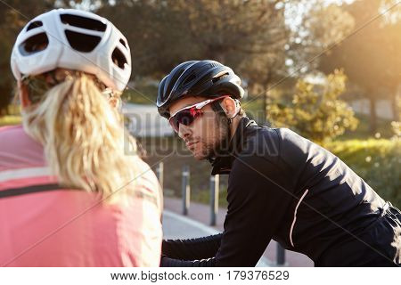 Attractive Young Bearded Male Rider Wearing Protective Equipment Talking Outdoors To Unrecognizable