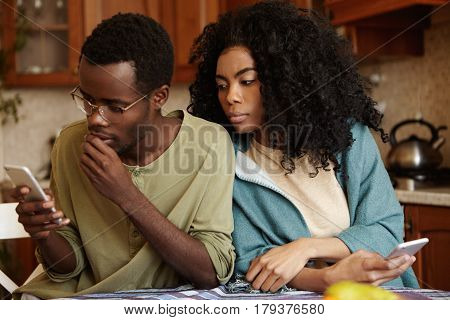 Worried Young Afro-american Man Wearing Glasses Typing Sms On Smart Phone Deep In Thoughts Without N