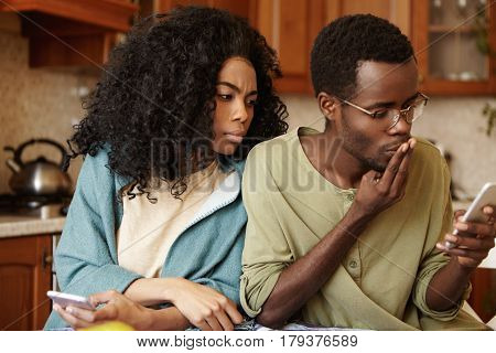 Suspicious Jealous Young African American Wife Looking Over Her Husband's Shoulder, Reading Messages