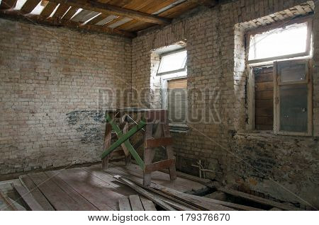 The process of building reconstruction. Old room with brick walls boarded up windows wooden ceiling and broken floor.