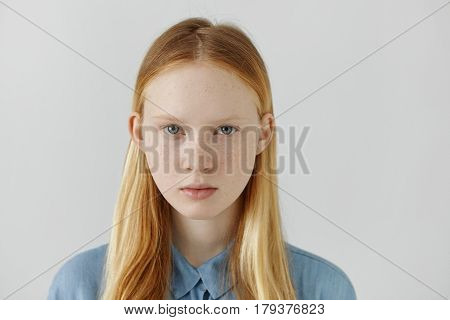 Headshot Of Caucasian Girl With Freckles, Blond Hair And Light Eyes Dressed In Blue School Shirt Sta