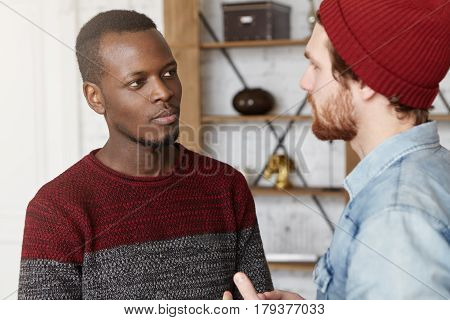 Interracial Friendship, People, Youth And Happiness. Stylish Bearded Hipster In Hat Explaining Somet