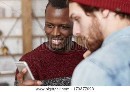 Excited Happy Young Black Man In Sweater Showing His Fashionable White Friend Inspiring Blog Account