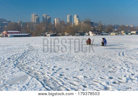 Dnepr, Ukraine - January 19, 2017: Winter landscape with fishermen on a frozen river Dnepr in center of the same city Ukraine