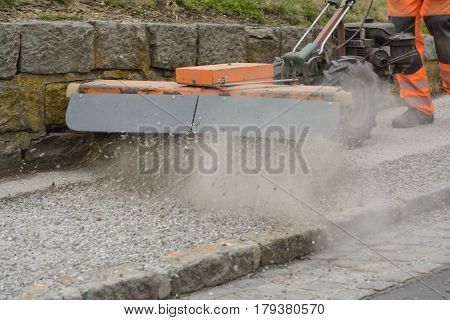 Sweeper cleans bourgeon dough from loose chippings - close-up
