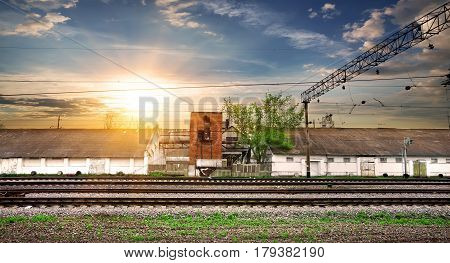 Rails and industrial station at the sunset