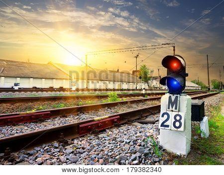 Railway semaphore near industrial station at sunset