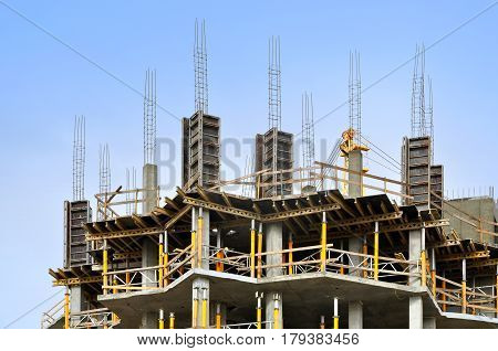 The process of construction of multistory monolithic building. Concrete and metal frame of floor slabs and columns.