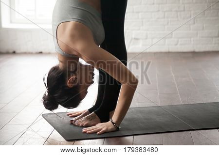 Young attractive woman practicing yoga, standing forward bend exercise, head to knees, uttanasana pose, working out, wearing sportswear bra and pants, white loft studio background, closeup