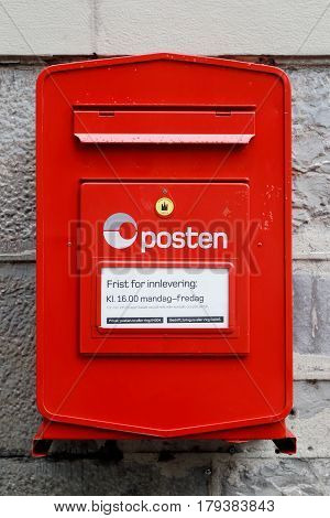 Trondheim Norway - September 30 2016: Close up of red Norwegian post box operated by the Norwegian postal service Posten. The white label indicates that letters are collected at 4 p.m Monday to Friday.