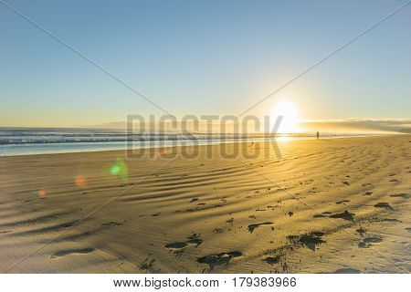 Golden hue of sunrise over wide flat sandy beach at Ohope Whakatane New Zealand with distant silhouette of man walking small dog.