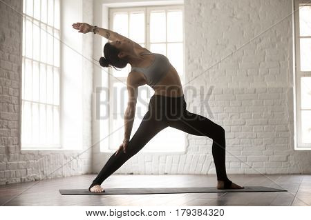 Young attractive woman practicing yoga concept, standing in Reverse Warrior exercise, Viparita Virabhadrasana pose, working out wearing sportswear, full length, white loft studio background, side view