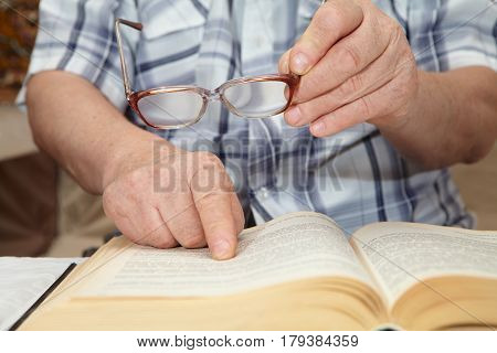 An Elderly Man With Glasses Reading A Book