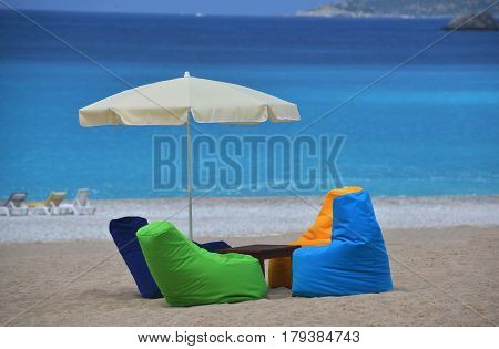 Bright multicolored seats and sunshade on beach. Sand equipped beach. Blue sea in the background.
