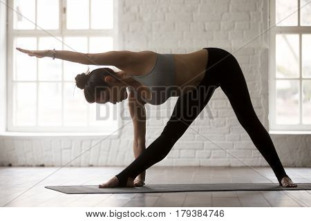Young yogi woman practicing yoga concept, standing in Utthita Trikonasana exercise, extended triangle pose, working out, wearing sportswear, full length, white loft studio background, side view
