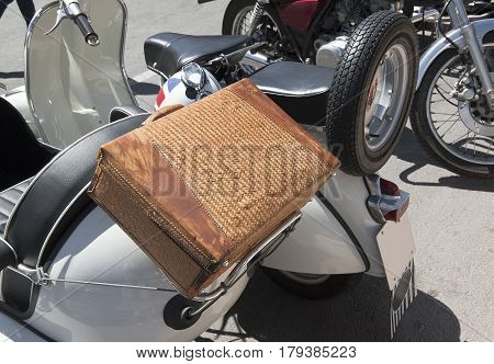 braided leather suitcase in the trunk of a motorcycle closeup