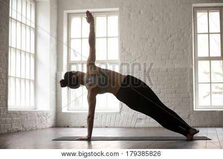 Young attractive yogi woman practicing yoga concept, standing in Side Plank exercise, Vasisthasana pose, working out, wearing sportswear, full length, white loft studio background, rear view