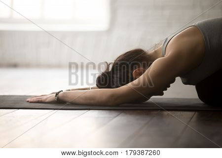 Young attractive sporty yogi woman practicing yoga concept, sitting in Child exercise, Balasana pose, working out, wearing sportswear, close up, white loft studio background, side view