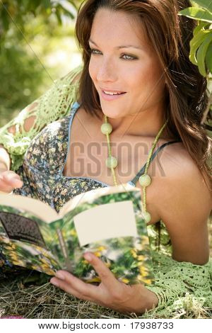 Beautiful woman reading happy a book in forest, green nature outdoor