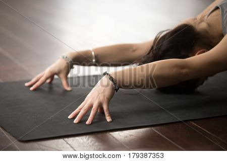 Young attractive sporty woman practicing yoga, sitting in Child exercise, Balasana pose, working out wearing sportswear and elegant wrist bracelets accessories, close up studio wooden floor background