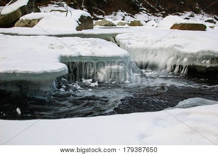 The mountain river is running swiftly under a thick crust of ice. Ice crystals shine in the sun.