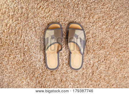 Gray leather slippers stand in the middle of a beige fleecy carpet