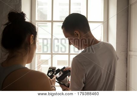 Young female and photographer working together on sport photo shoot, looking through pictures, choosing. Fit model posting image in social media using smartphone. Teamwork, healthy lifestyle concept