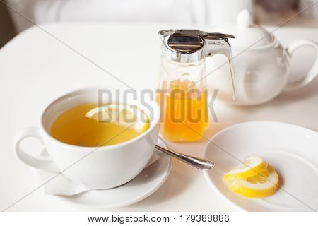 Cup of hot green tea with lemon on white table, fresh lemon and honey - closeup shot. Sun light flair effect. Nice interior in wooden house. Relaxation concept.