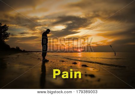 Creative conceptual,Pain,word on photo with man alone on the beach during sunset.Calm sea with rippling waves.