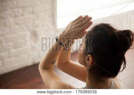 Young attractive yogi woman practicing yoga concept, doing namaste gesture, namaste hands to forehead, working out, wearing wrist bracelets, studio background, closeup, view over the shoulder