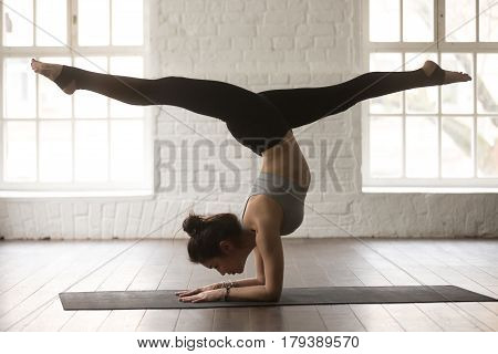 Young attractive yogi woman practicing yoga concept, standing in variation of Pincha Mayurasana exercise, handstand pose, working out, wearing sportswear, full length, white loft studio background