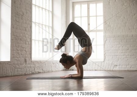 Silhouette of young cool attractive yogi woman practicing yoga concept, doing vrischikasana exercise, Scorpion pose, working out, wearing black sportswear, full length, white loft studio background