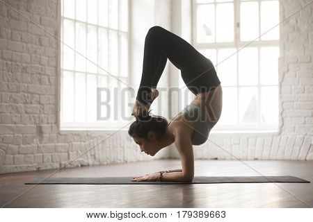 Silhouette of young cool yogi woman practicing yoga concept, stretching in vrischikasana exercise, Scorpion pose, working out, wearing black sportswear pants, full length, white loft studio background