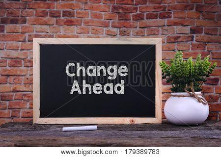 Change Ahead Word On Blackboard With Green Plant.