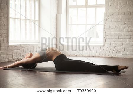 Young attractive yogi woman practicing yoga concept, stretching in Matsyasana exercise, Fish pose, working out, wearing black sportswear, full length, white loft studio background