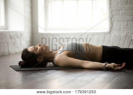 Young attractive yogi woman practicing yoga concept, lying in Dead Body, Savasana exercise, Corpse pose, working out, wearing sportswear, close up portrait, white loft studio background