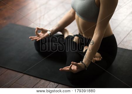 Close up of young woman with tattoo and nice wrist bracelets practicing yoga, sitting in Padmasana exercise, Lotus pose with mudra, working out on black mat, wearing sportswear, studio background