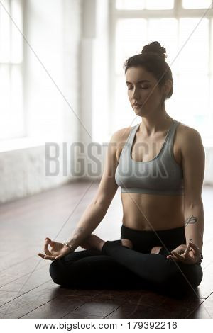 Young yogi woman practicing yoga concept, sitting in Padmasana exercise, Lotus pose with mudra, working out, wearing sportswear, grey top, black pants, full length, white loft studio background