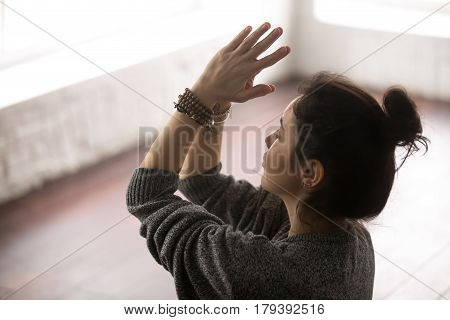 Young attractive yogi woman practicing yoga concept, making namaste gesture, working out, wearing grey oversized sweater, closeup, white loft studio background, horizontal photo