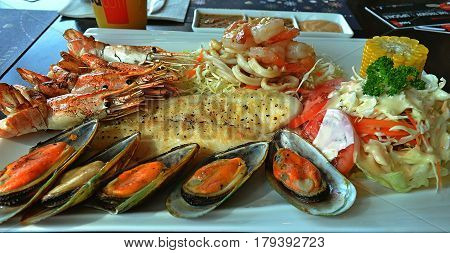 The restaurant treats its guests with seafood and vegetables. A pleasant scallop, tasty shrimp and a wonderful fish decorated with a green salad and golden corn.