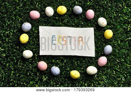 Easter cross stitched on textile isolated on artificial grass displayed with speckled eggs