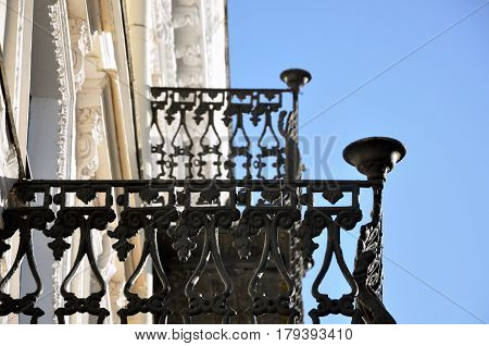 Looking up at two old black wrought iron balconies closeup. Selective focus.