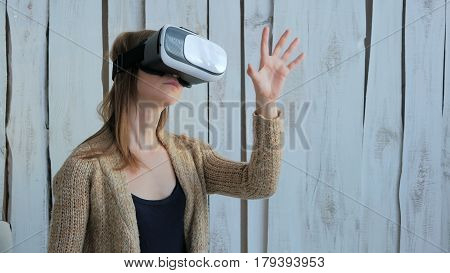 Young woman using Virtual Reality Glasses. Virtual reality mask. VR. White wooden background. Future and technology concept