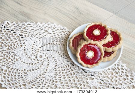 Cozy home still life. Plate of cookies with red jelly on white knitted napkin on light wooden background. Close up.