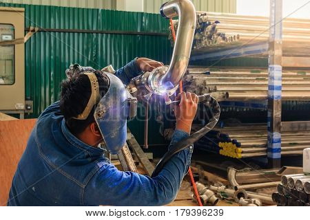 Industrial worker with protective mask welding metal piping using tig welder