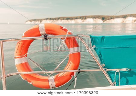 Detailed close up of rescue ring on sailing boat handrail during cruise on water Sassnitz cliff in background.