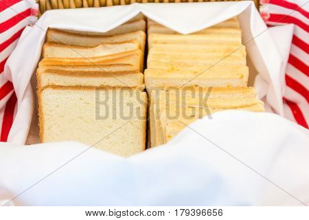 Toast bread in a basket. Wholemeal toast bread slices placed on a cotton cloth napkin in a wicker basket Close up